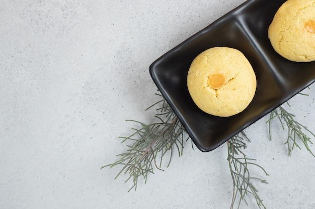白い表面に2つの丸い甘いクッキーが付いた暗いプレート