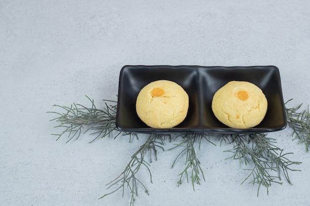 흰색 표면에 두 개의 둥근 달콤한 쿠키가 있는 어두운 접시