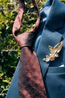 Темно-красный галстук и синий пиджак с бутоньеркой на зеленых листочках.