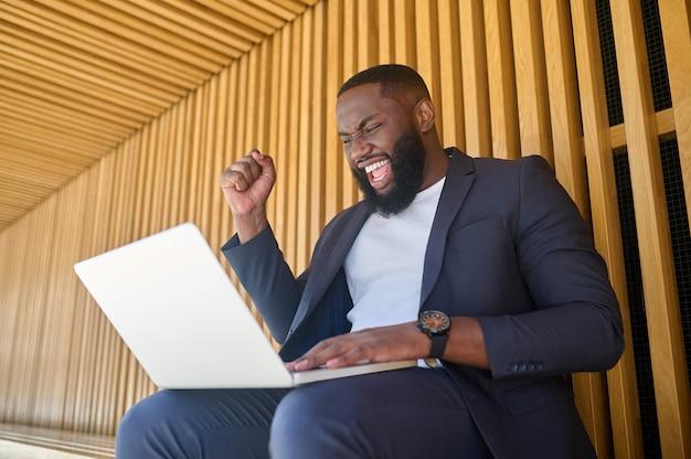 벤치에 앉아서 일하는 노트북을 들고 있는 검은 피부의 사업가