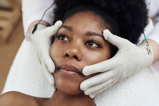 Темнокожая модель лежит на кушетке у косметолога и получает микротоковый массаж.