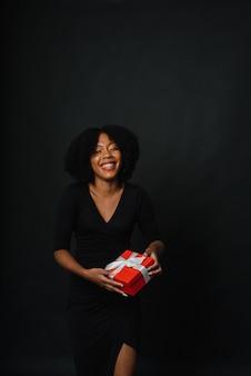 아프리카 헤어스타일에 검은 피부의 여성이 카메라에 선물을 주고 있다. 새해 쇼핑, 선물의 개념. 공간을 복사합니다.