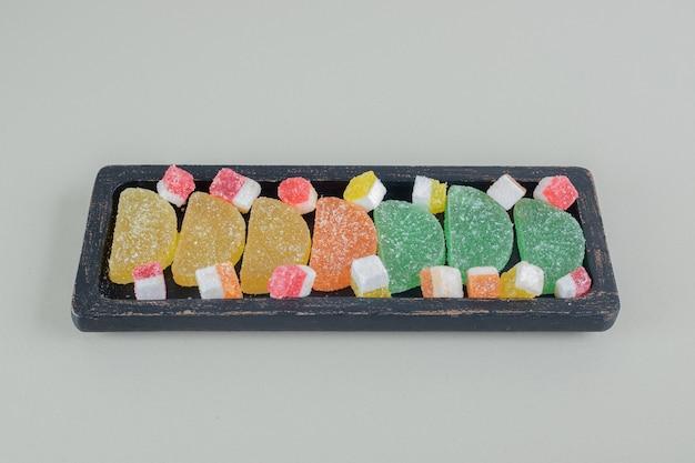 色とりどりの砂糖の入ったマーマレードでいっぱいの暗い木の板。