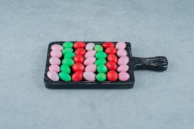 흰색 표면에 둥근 달콤한 다채로운 사탕으로 가득한 어두운 나무 보드
