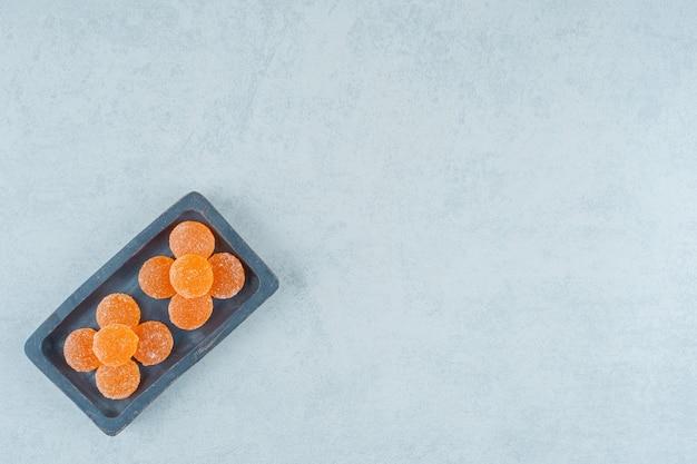 白い背景の上の甘いオレンジ色のゼリーキャンディーでいっぱいの暗い木の板。高品質の写真
