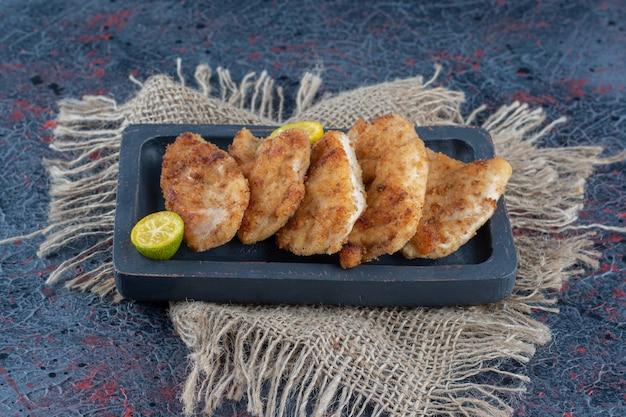 Темная деревянная доска с запеченным куриным мясом с дольками лимона.