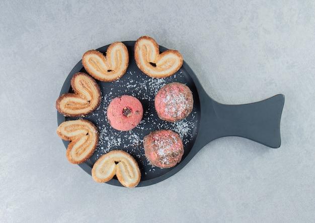 달콤한 하트 모양의 쿠키가 있는 짙은 나무 판자.