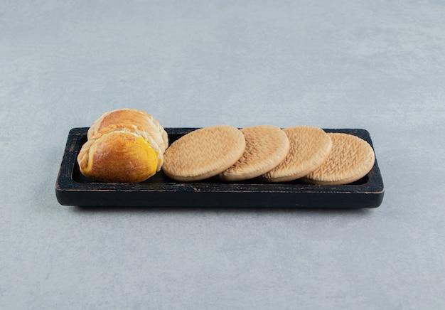 Темная деревянная доска с круглым сладким печеньем.