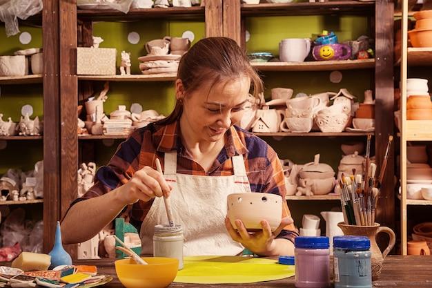 Темноволосая девушка, гончар в клетчатой рубашке и фартуке, раскрашивает глиняную чашу в серый цвет.