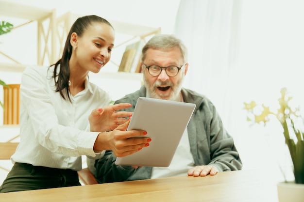 Дочь или внучка проводит время с дедушкой или старшим мужчиной. семья или день отца, эмоции и счастье. портрет образа жизни дома. девушка заботится о папе. с помощью планшета.