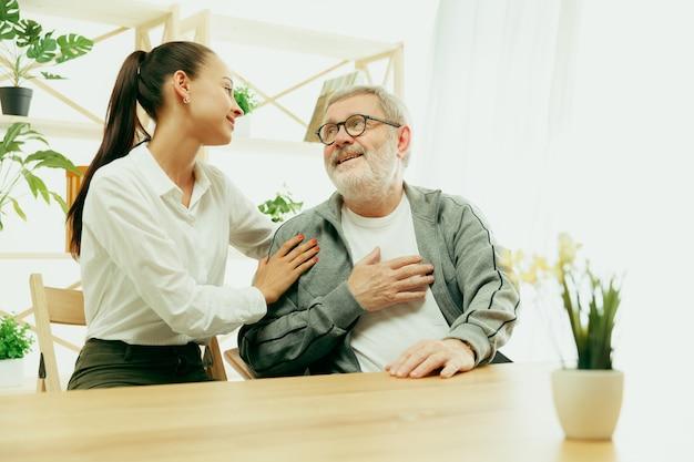 Дочь или внучка проводит время с дедушкой или старшим мужчиной. день семьи или отца, положительные эмоции и счастье. портрет образа жизни дома. девушка заботится о папе.