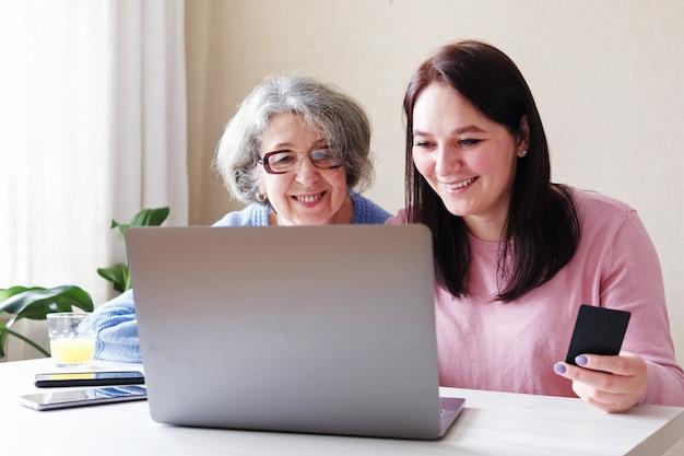 Дочь с пожилой мамой делает покупки в интернете