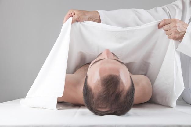 시체 보관소에 죽은 사람이 누워 있습니다.