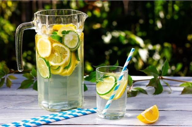 軽い木製のテーブルの上にレモンとライムのスライスと冷たい水のデカンター