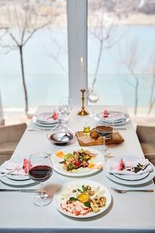Гостей ждет украшенный столик в ресторане с бокалами красного вина и закусками.
