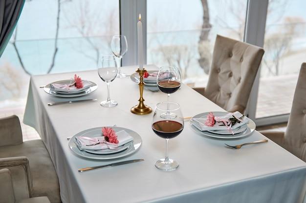 Гостей ждет украшенный столик в ресторане с бокалами красного вина и зажженной свечой.