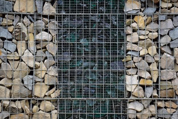Декоративный забор из камней за решеткой и разбитого большого стекла посередине. сфотографирован полный кадр