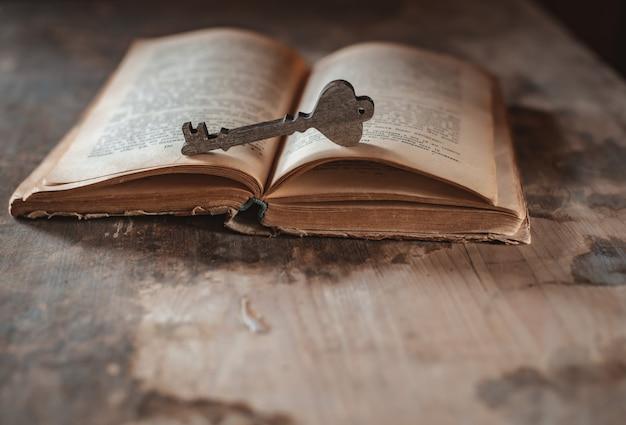 開いた古いヴィンテージの本に装飾的な木製の鍵がかかっている