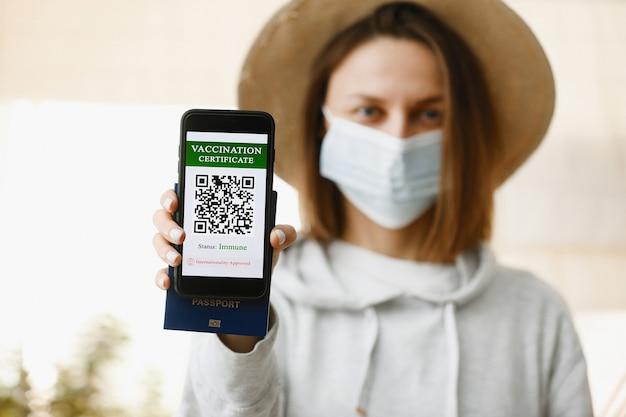 焦点がぼけた少女は、covid-19病に対する予防接種の証明書が付いたパスポートとスマートフォンを持っています