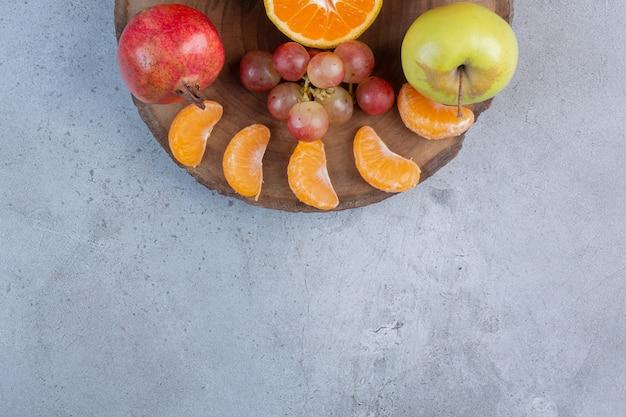 大理石の背景の木の板にフルーツのおいしいサービング。