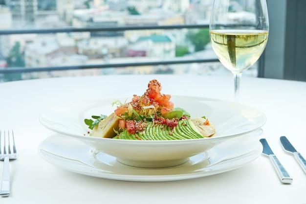 아티 초크, 아보카도, 참치, 퀴 노아를 곁들인 맛있고 건강한 샐러드는 흰색 식탁보에 흰색 접시에 제공됩니다.