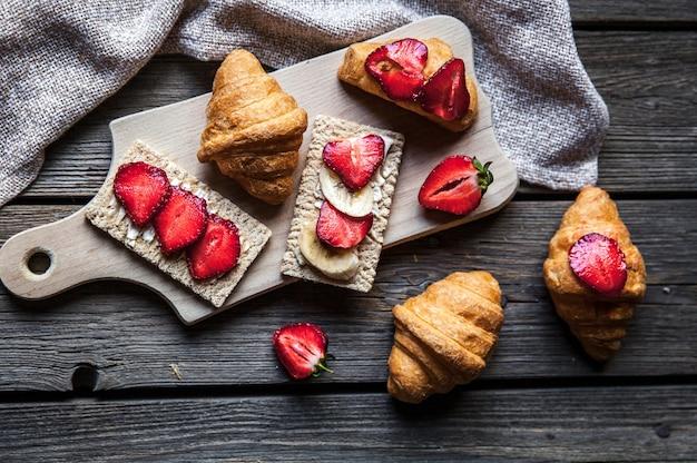 木製のテーブルにイチゴとパンのおいしい朝食。果物、食べ物、サンドイッチ、チーズ。ビンテージ・スタイル。そして