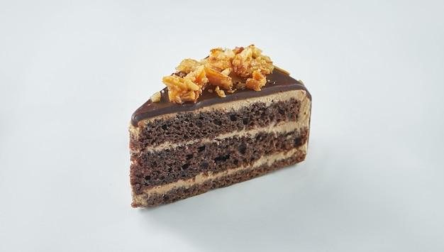 白いテーブルにアーモンドとキャラメルが入った美味しいチョコレートケーキ。クローズアップ、セレクティブフォーカス