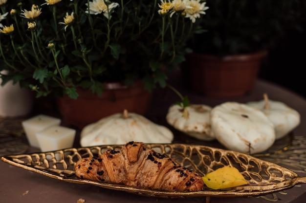 На деревянном столе возле цветущих хризантем лежит вкусный круассан.