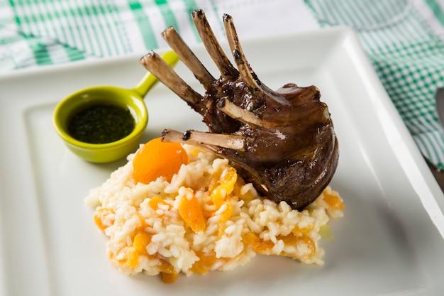 정사각형 접시에 밥과 살구를 곁들인 양고기 랙의 맛있는 요리.