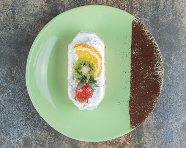 緑のプレートにフルーツが入ったおいしいエクレア