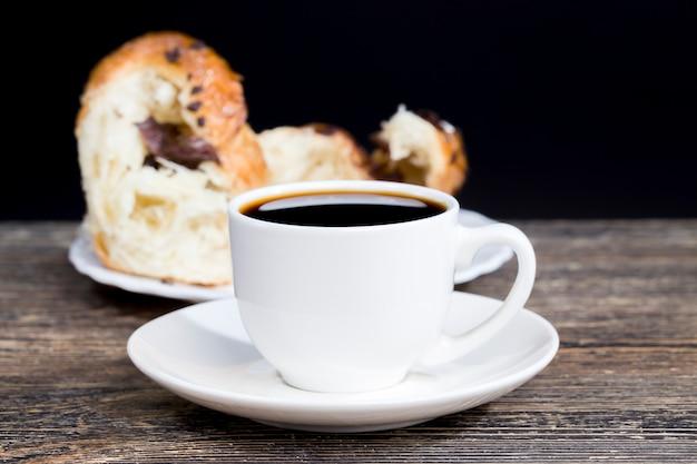 おいしい淹れたてのパンと一杯のブラックアロマコーヒー、淹れたてのブラックコーヒーと小さなデザートが一緒に横たわっています。ケータリングサービスの料理とチョコレートのカップケーキ