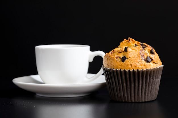 Вкусная свежая булочка и чашка черного ароматного кофе, свежесваренный черный кофе и небольшой десерт - все вместе.