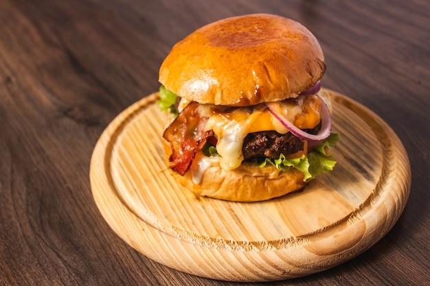 Вкусный гамбургер с беконом и овощами на деревянной тарелке.