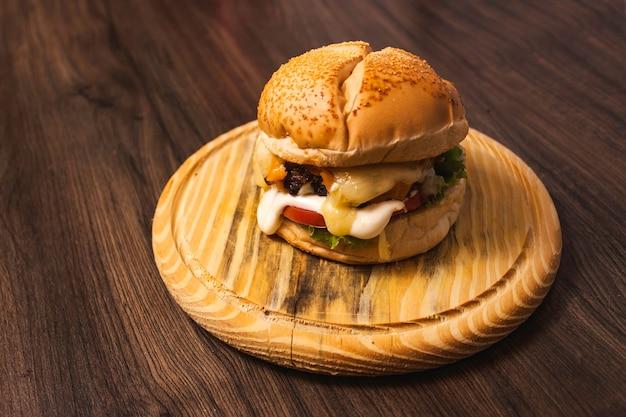 Вкусный гамбургер с разными видами сыра на деревянной тарелке.
