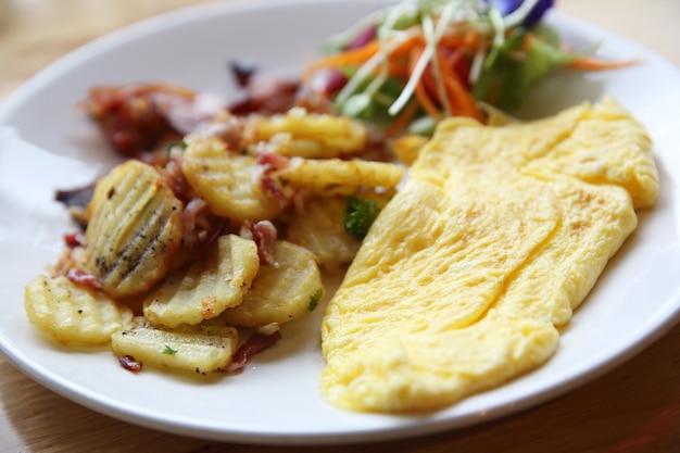 Вкусный домашний завтрак с хрустящим беконом и яичным омлетом.