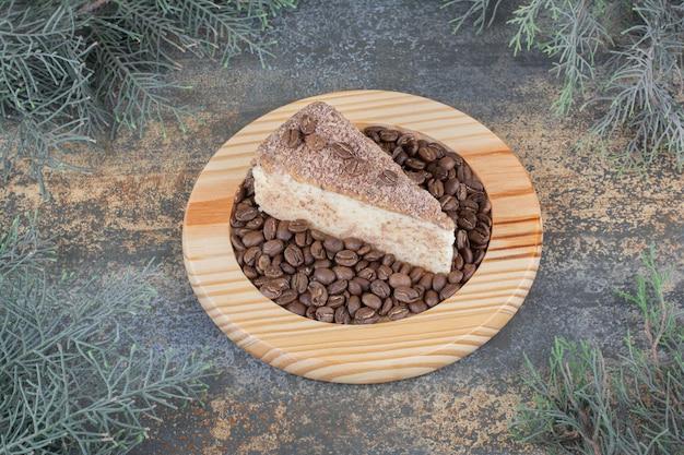 Вкусный кусок торта с кофейными зернами на деревянной доске. фото высокого качества