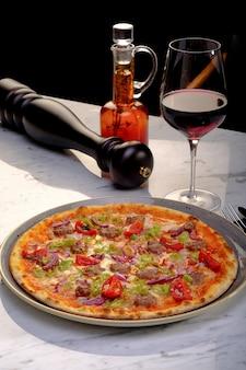 レストランで赤ワインを片手に美味しいピザ