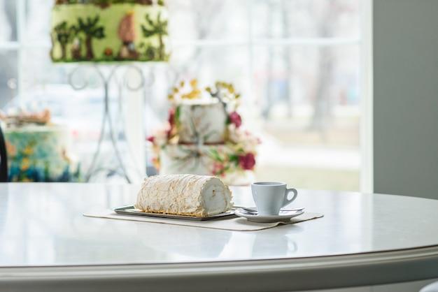 居心地の良い喫茶店のテーブルでベズルコフのおいしいロールとコーヒーのカップ