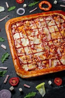 ベーコンとチーズが入った美味しいスクエアクラストフラットブレッドピザ。暗い背景にオリーブと赤ピーマンを添えた新鮮な自家製イタリアンピザマルゲリータ