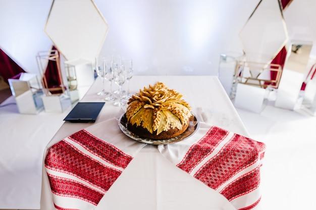 Вкусный сладкий свадебный каравай в украинском стиле на вышитых полотенцах. праздничный сладкий стол.
