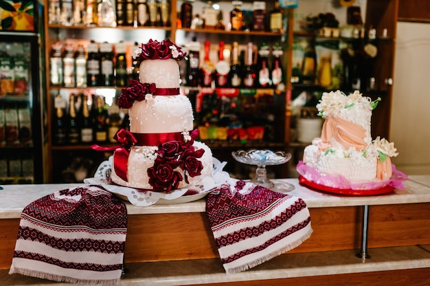 Вкусный сладкий свадебный каравай в украинском стиле на вышитых полотенцах.
