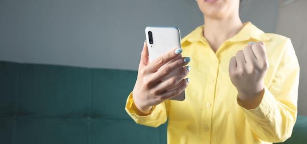 喜んでいる若い女の子は一人でソファに座って、彼女の電話を保持し、灰色の背景に対して彼女の拳を上げます