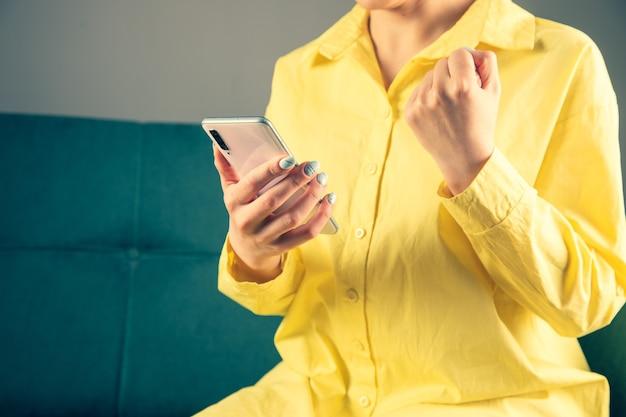 Обрадованная девушка сидит на диване одна, держит телефон и поднимает кулак на серую стену.