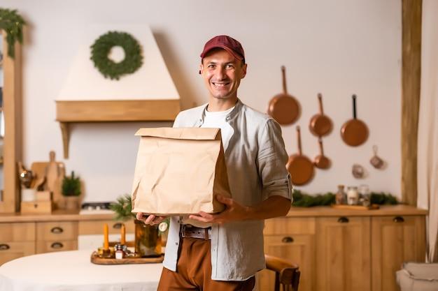 Курьер с пакетом еды стоит в новогоднем интерьере