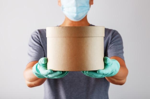 ゴム手袋とマスクの配達サービス宅配便が小包を保持します。