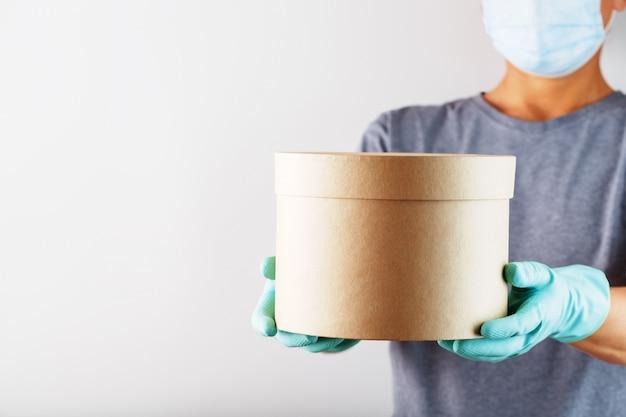 配達サービスの従業員は、白い背景にウイルスや病気からそれを保護するための手袋とマスクが入った箱を持っています。