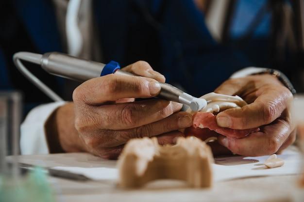 Зубной техник обрабатывает слепок с челюсти пациента.