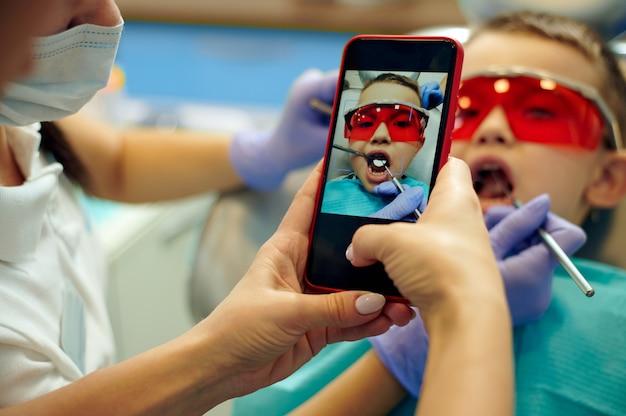 歯科医院での歯の治療中に歯科用椅子に座っている少年の写真撮影をしている歯科助手。スマートフォンに焦点を当てる