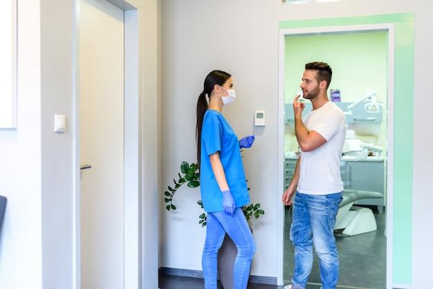 Стоматолог обсуждает лечение с пациентом в стоматологической студии