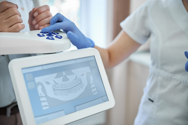 Стоматолог нажимает кнопки на панорамном рентгеновском аппарате, помогая пациенту сделать стоматологический рентген